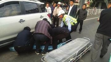 骑车女子被压车轮下 十多名路人抬车救人