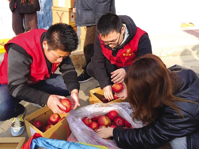 青年志愿者帮着果农卖苹果